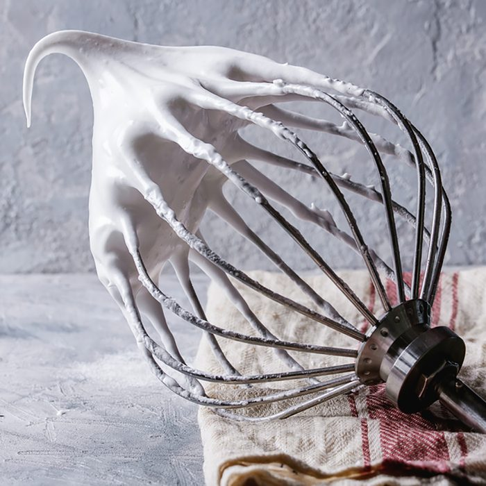 Whipped meringue on a stand mixer's whisk.
