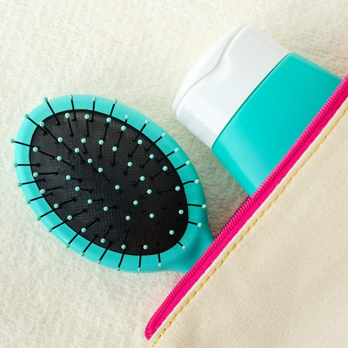 Hair shampoo (mask, conditioner, face cream, sunscreen lotion) and hair brush in the small make-up pouch. Top view, copy space.