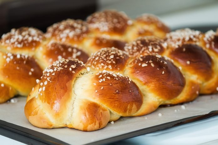 Freshly baked sweet braided bread loaf on a baking sheet