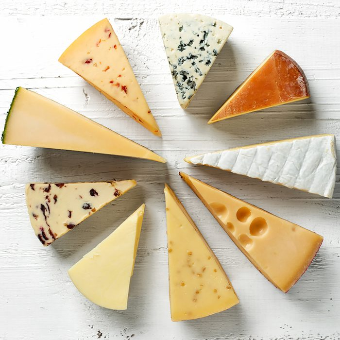 various types of cheese on white wooden table