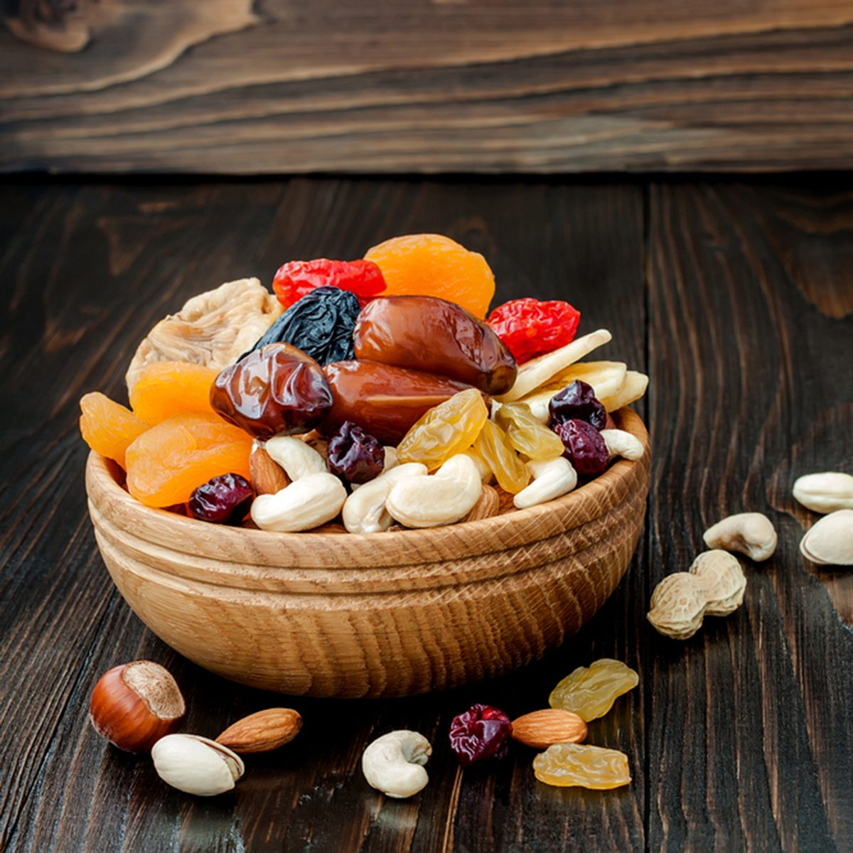 Mix of dried fruits and nuts on dark wood background