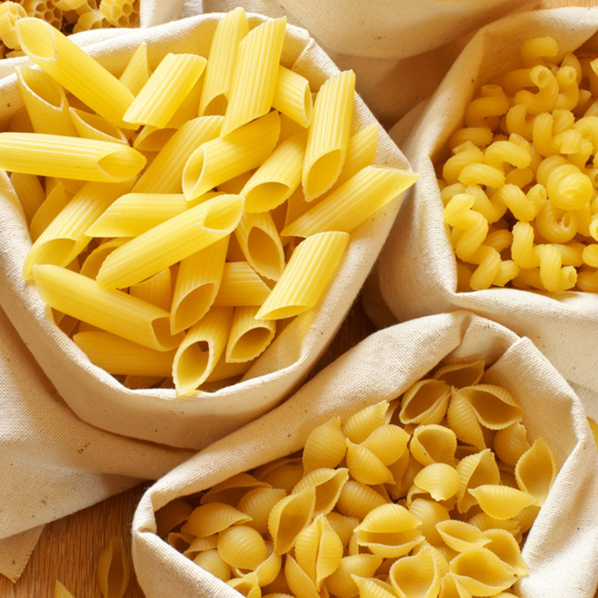 Close-up of assorted pasta in jute bags.