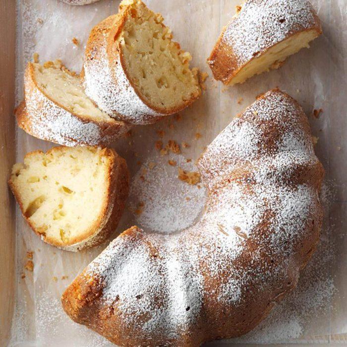 A round bundt apple cake with powdered sugar on top.