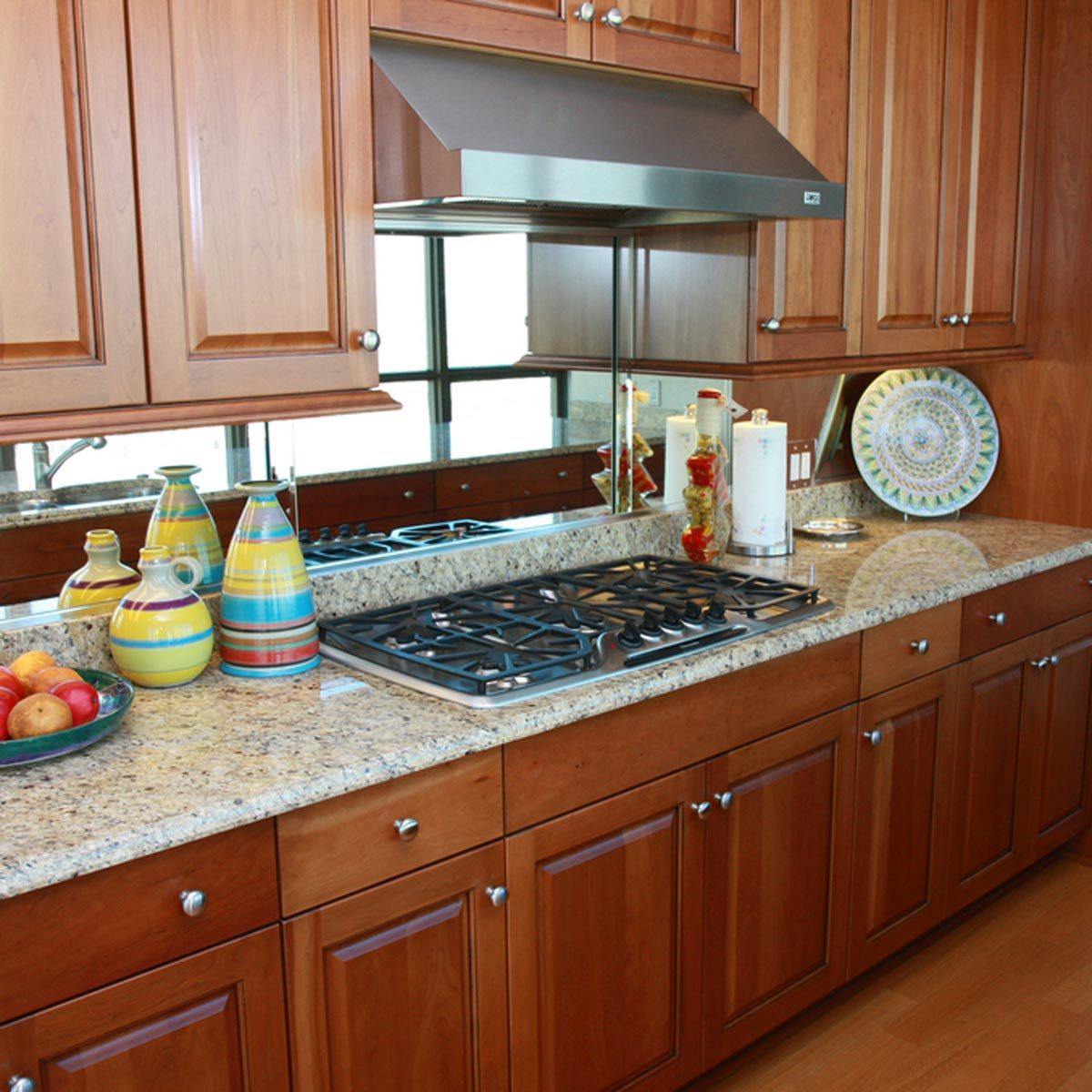 Kitchen with wooden cabinets and a mirror backsplash