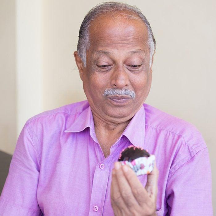 Closeup portrait of elderly gentleman in pink shirt craving dessert