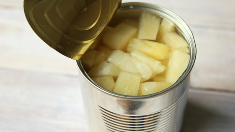 Opened tin can of canned pineapple pieces.