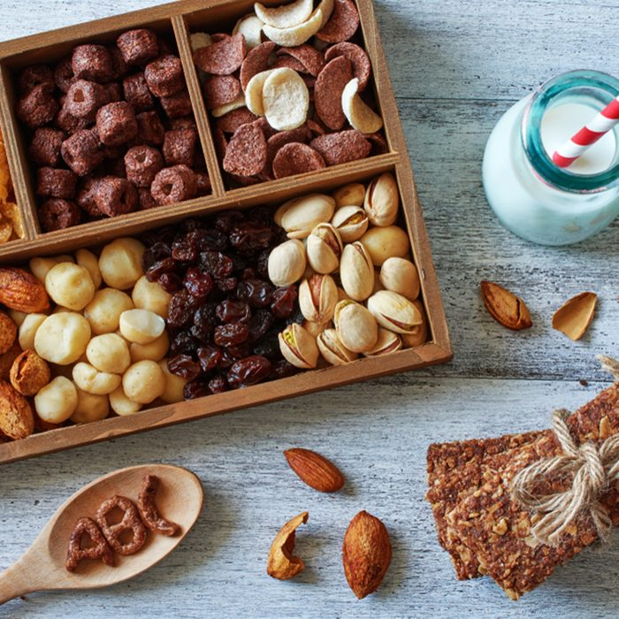 Top view of variety of nuts, cereal and raisin in wooden box