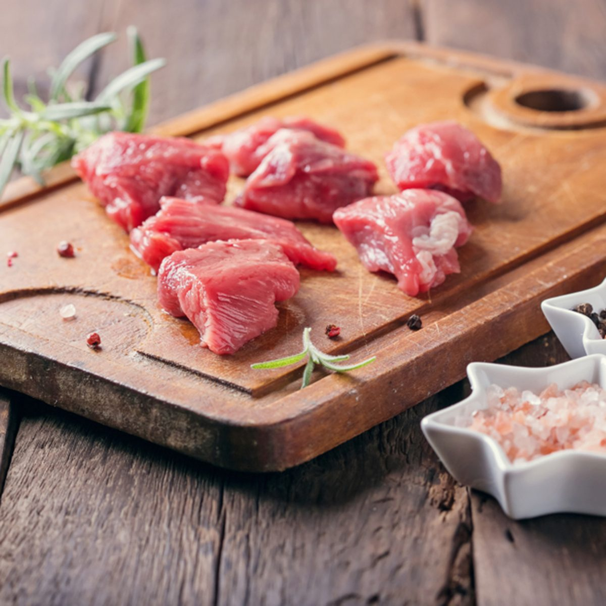 raw meat prepared for cooking on a kitchen board