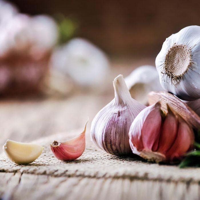 Garlic cloves on rustic table. Garlic in wooden bowl. Fresh peeled garlic and bulbs.