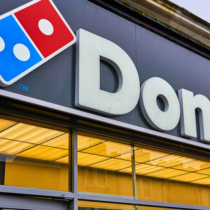 Domino's Pizza sign over the shop with the signature domino by the writing