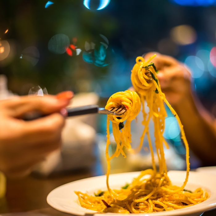 Spaghetti on a fork. Hand of two woman rolling spaghetti and keeping on a fork for eat.