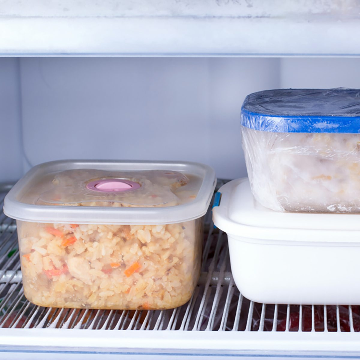 Frozen food in a container in the freezer. Refrigerator with frozen food. Ready meal;