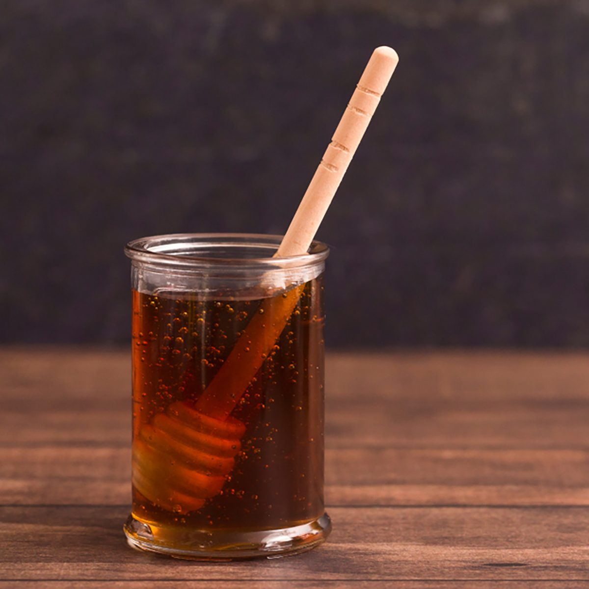 Honey with a Honey Spoon in a Glass Container