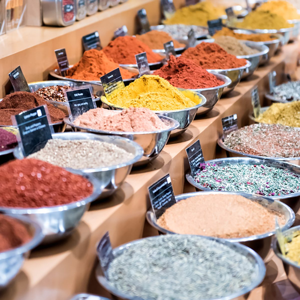 Many spices on display in bowls trays filled with herbs