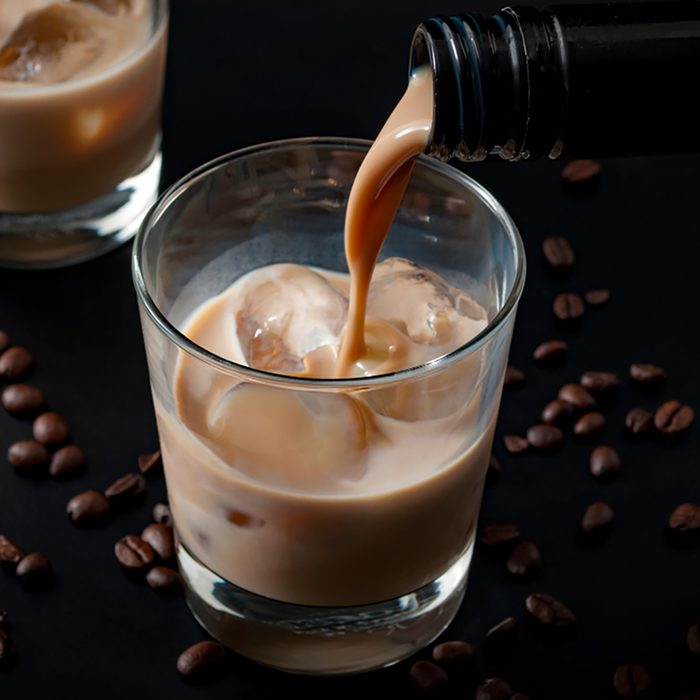 Pouring irish cream in a glass with ice, surrounded by coffee beans on a dark black background