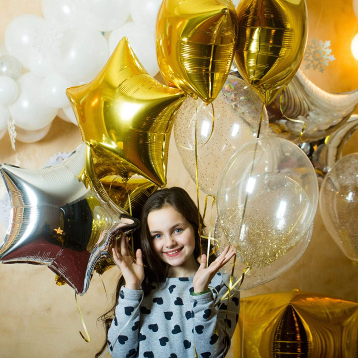 Little girl smile with golden silver star balloons
