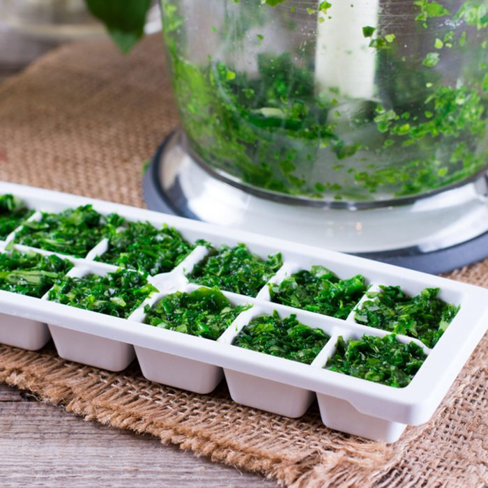 Frozen cubes of herbs on a wooden table
