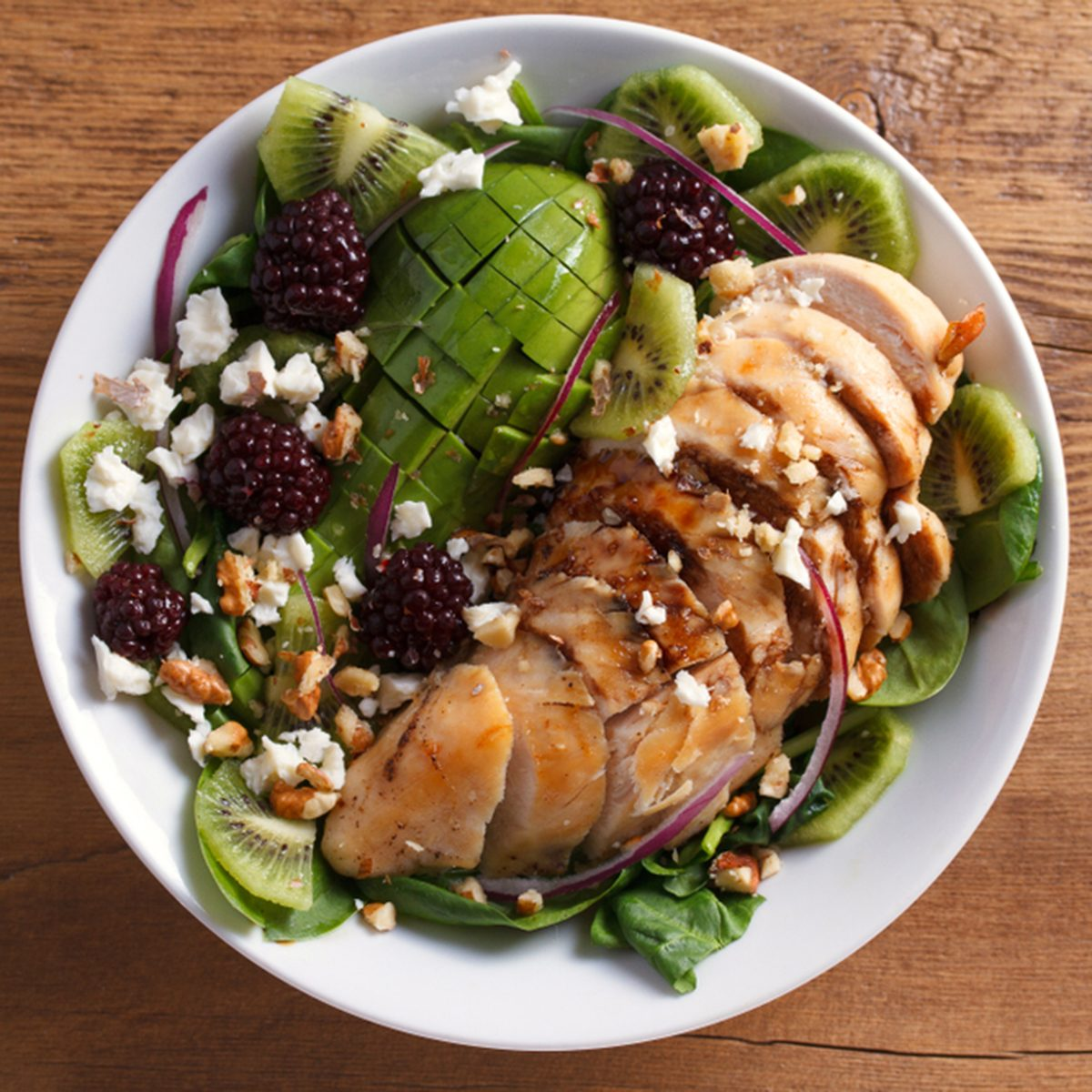 Kiwi blackberry balsamic chicken salad with avocado, spinach, feta cheese and walnuts.