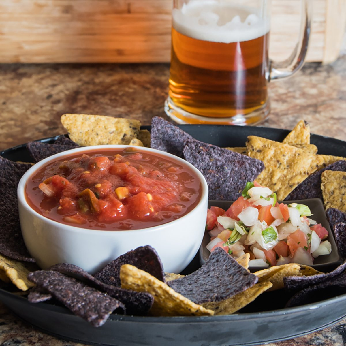 Platter with chips and salsa and pico de gallo and a beer