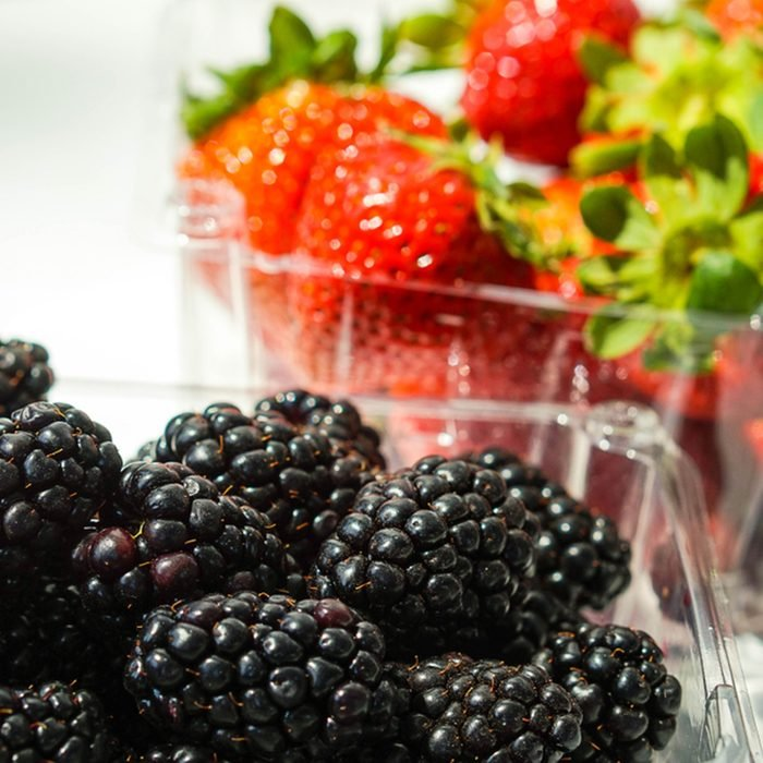 Blackberries in plastic container with strawberries in the background