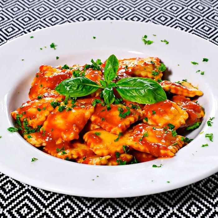 Fresh ravioli pasta with parsley and basil leaf, italian cuisine.