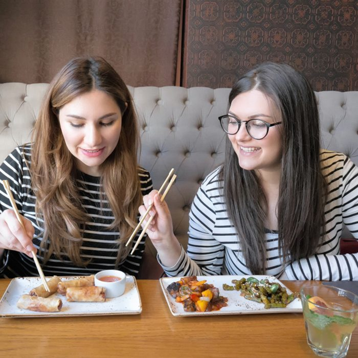 Lifestyle image of best friend girls ordering from menu in restaurant and deciding what to eat.