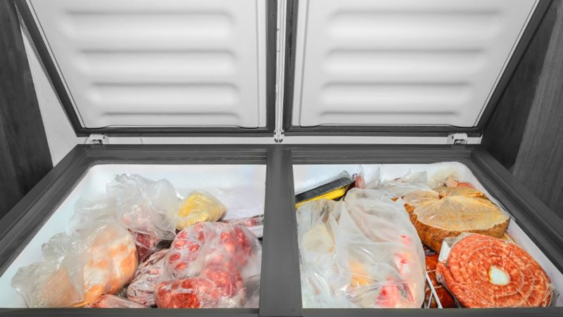 Frozen food in the freezer. Bagged frozen meat and other foods in a horizontal freezer with the two doors open.