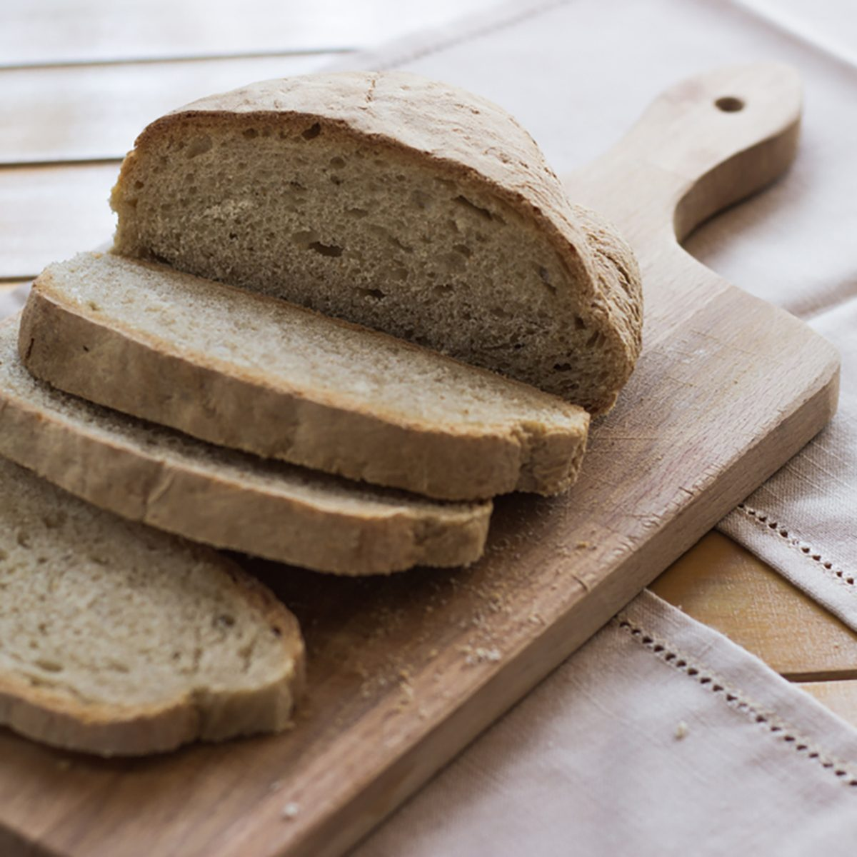 Bread and sliced bread on wooden cutting board on a table.