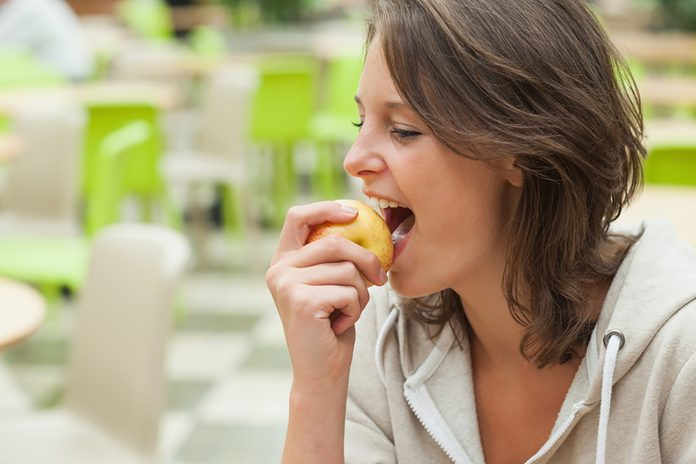 Close-up side view of a young woman eating apple in the cafeteria