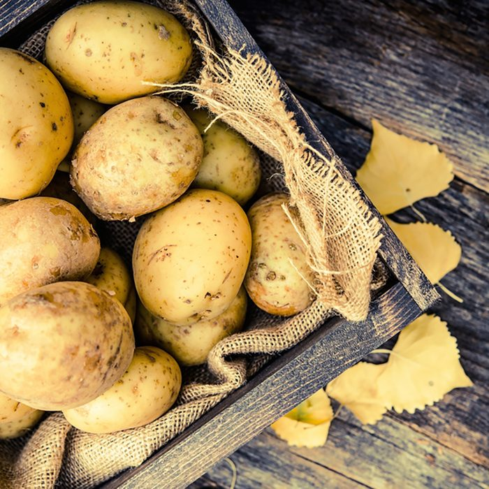Raw Organic Golden Potatoes in the Wooden Crate on Aged Wood Planks Table