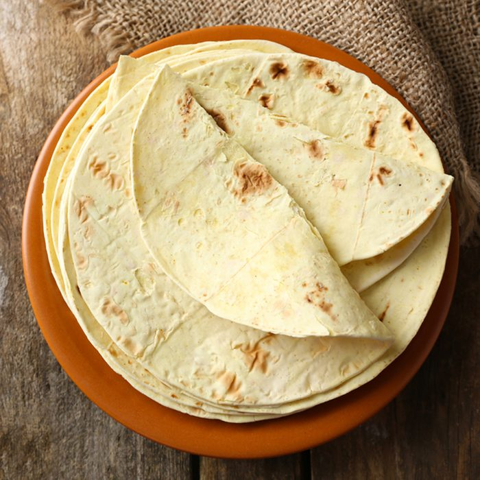 Stack of homemade whole wheat flour tortilla on plate
