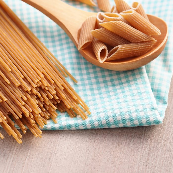 Whole wheat pasta - spaghetti and short pasta penne in wooden spoon on checkered table cloth on wooden table
