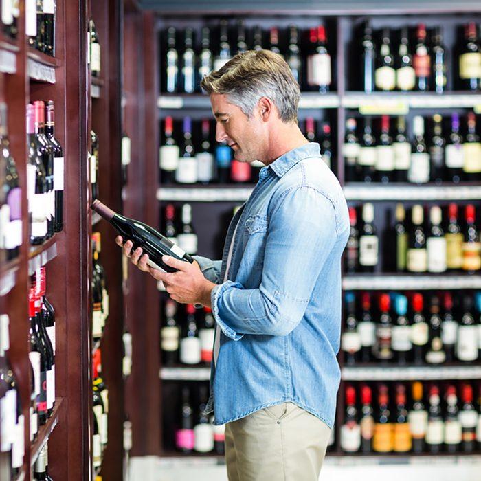 Smiling man holding bottle of wine in supermarket