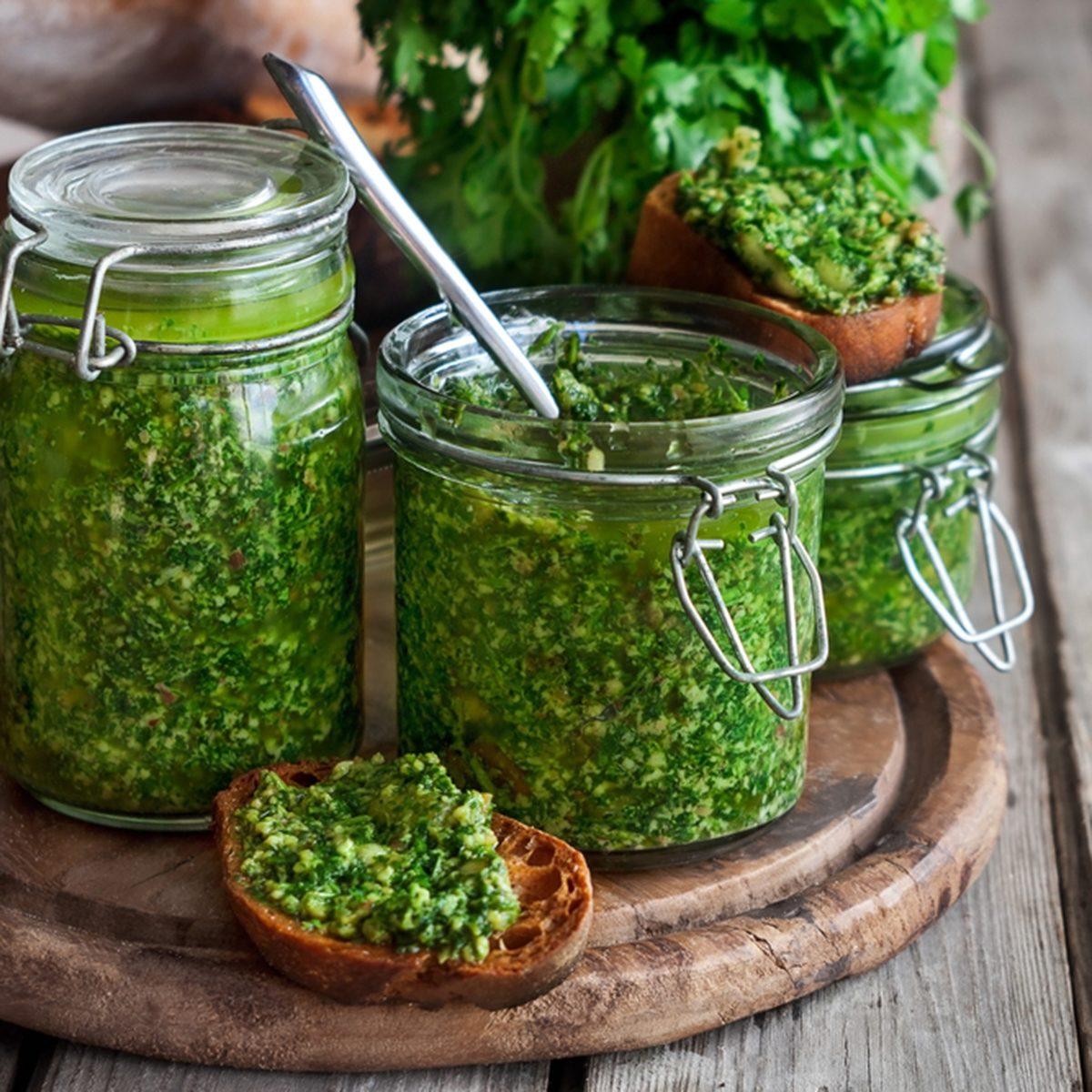 Homemade cilantro pesto in jars on wooden background