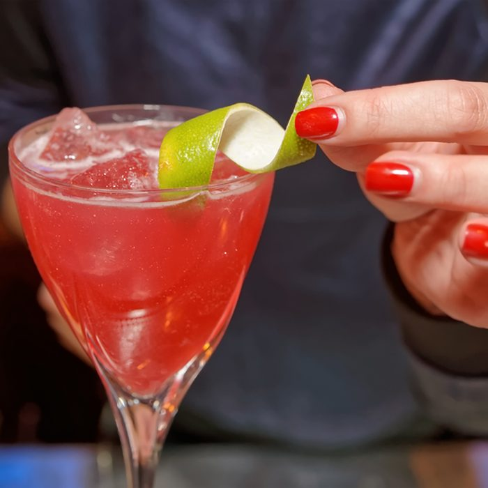 Female bartender is decorating a cocktail with lime zest