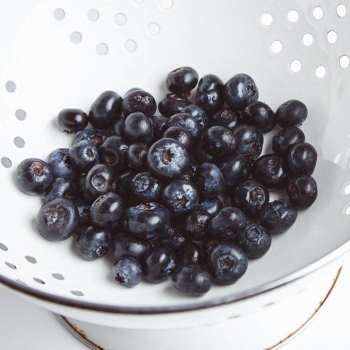 Heap of fresh blueberries in old enamel stainer