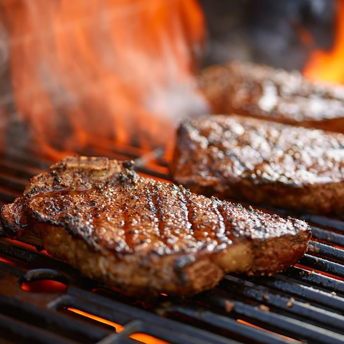 grilling steaks on flaming grill