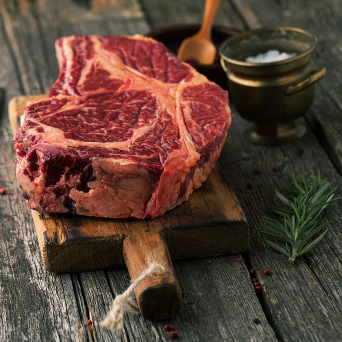 Raw fresh meat Ribeye Steak with pepper and salt on wooden background
