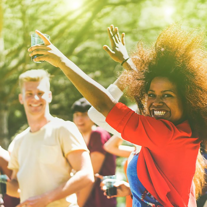 Multiracial young people dancing in forest party in summer time