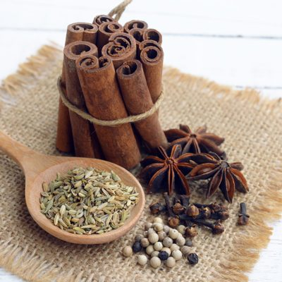 five spices (cinnamon, fennel, star anise, pepper, clove) to make chinese five-spice powder on wooden background