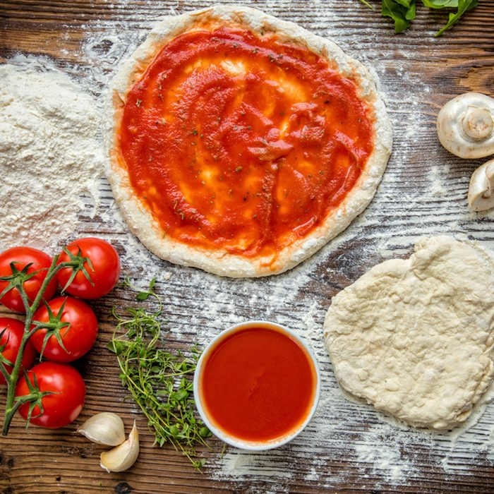 Pizza dough with ingredients and tomato sauce served on rustic wooden table.