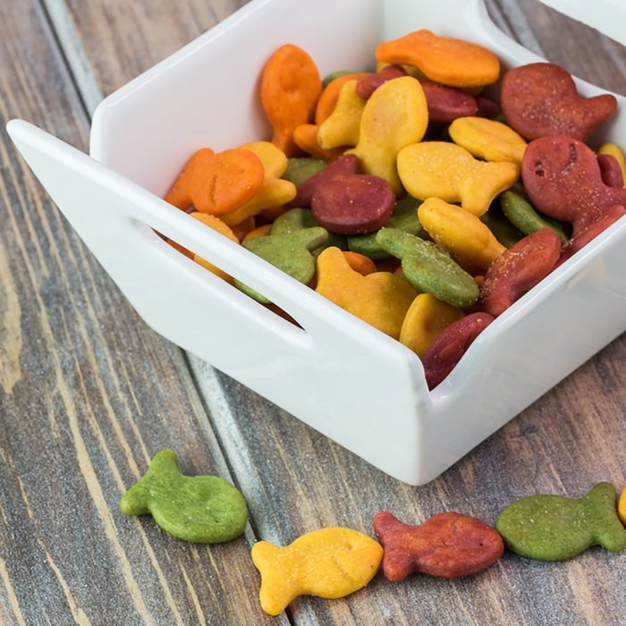 Close up of bowl with goldfish crackers on a wooden background.
