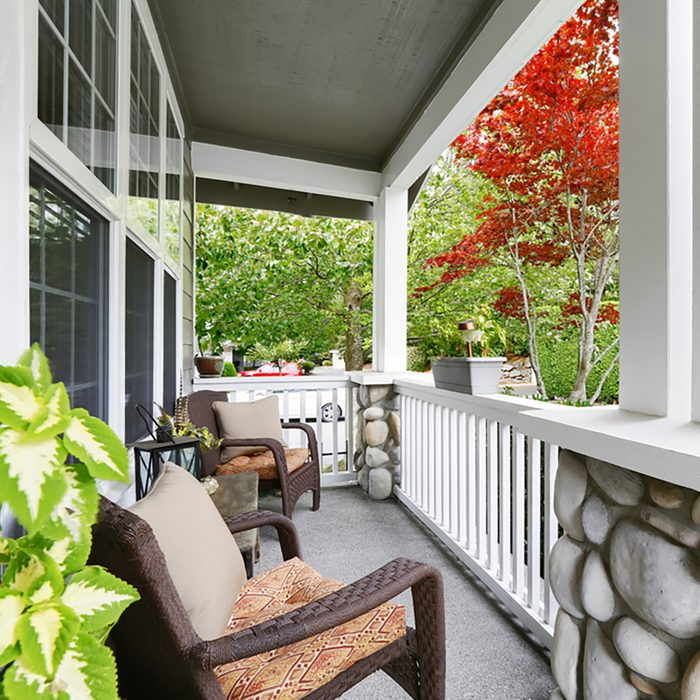 Cozy entrance porch with white columns decorated with stones and comfortable wicker chairs.