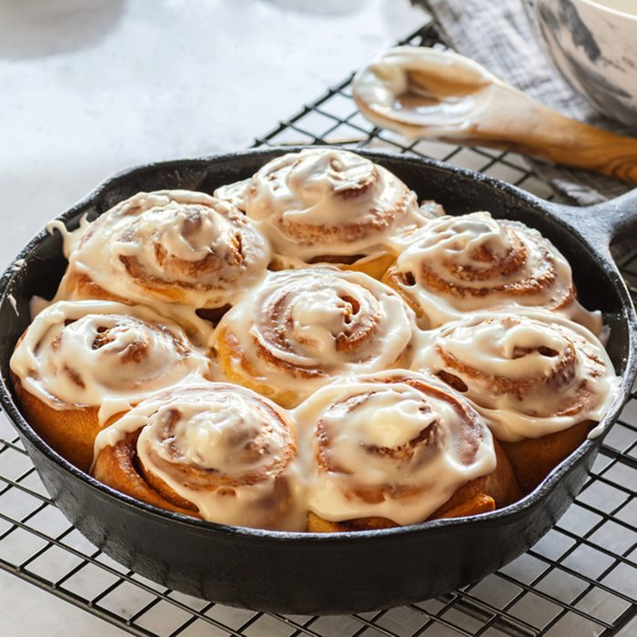 Cinnamon Rolls Baked in a Cast Iron Skillet with Cream Cheese Icing on a Cooling Rack
