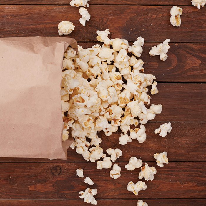 Popcorn in paper bag on wooden table
