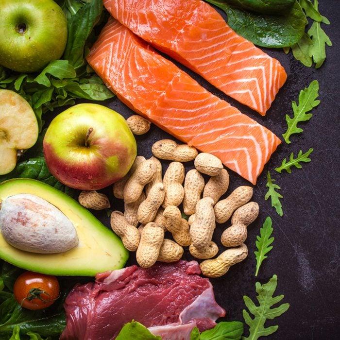 Fresh vegetables, fruits, fish, meat, nuts on black chalk board background.