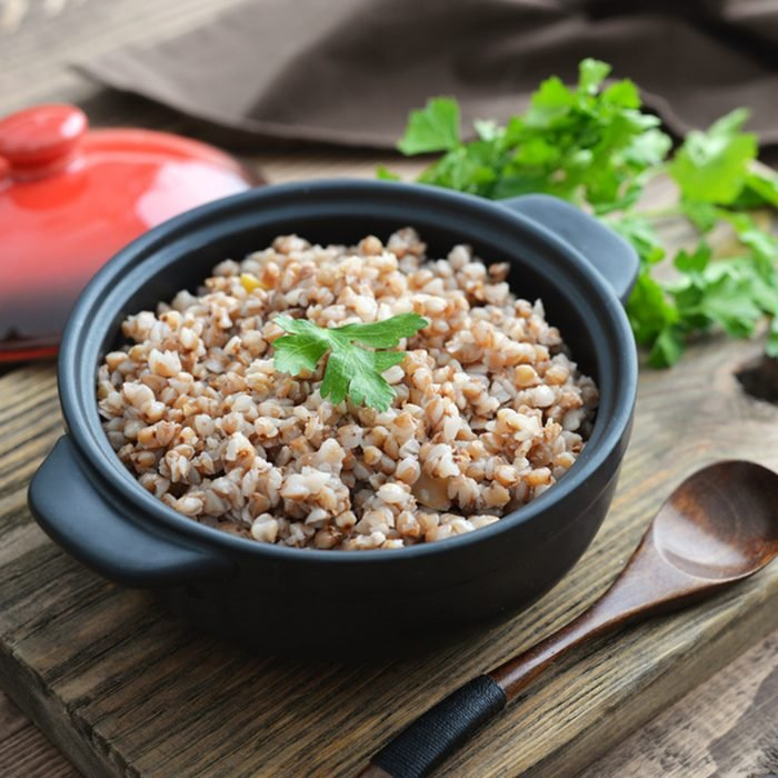 Buckwheat porridge in black casserole on wooden background closeup