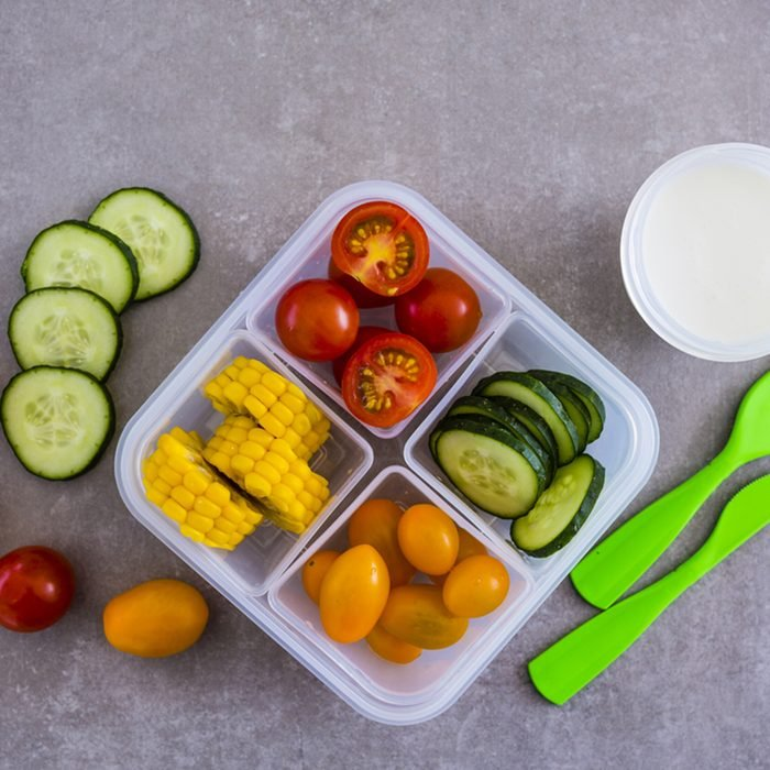 Tasty vegetarian take away food in plastic lunch box on light background.