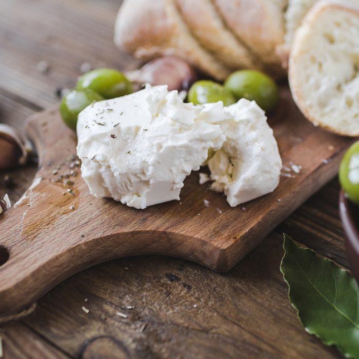 Green olives, sliced ciabatta, feta cheese on a wooden board