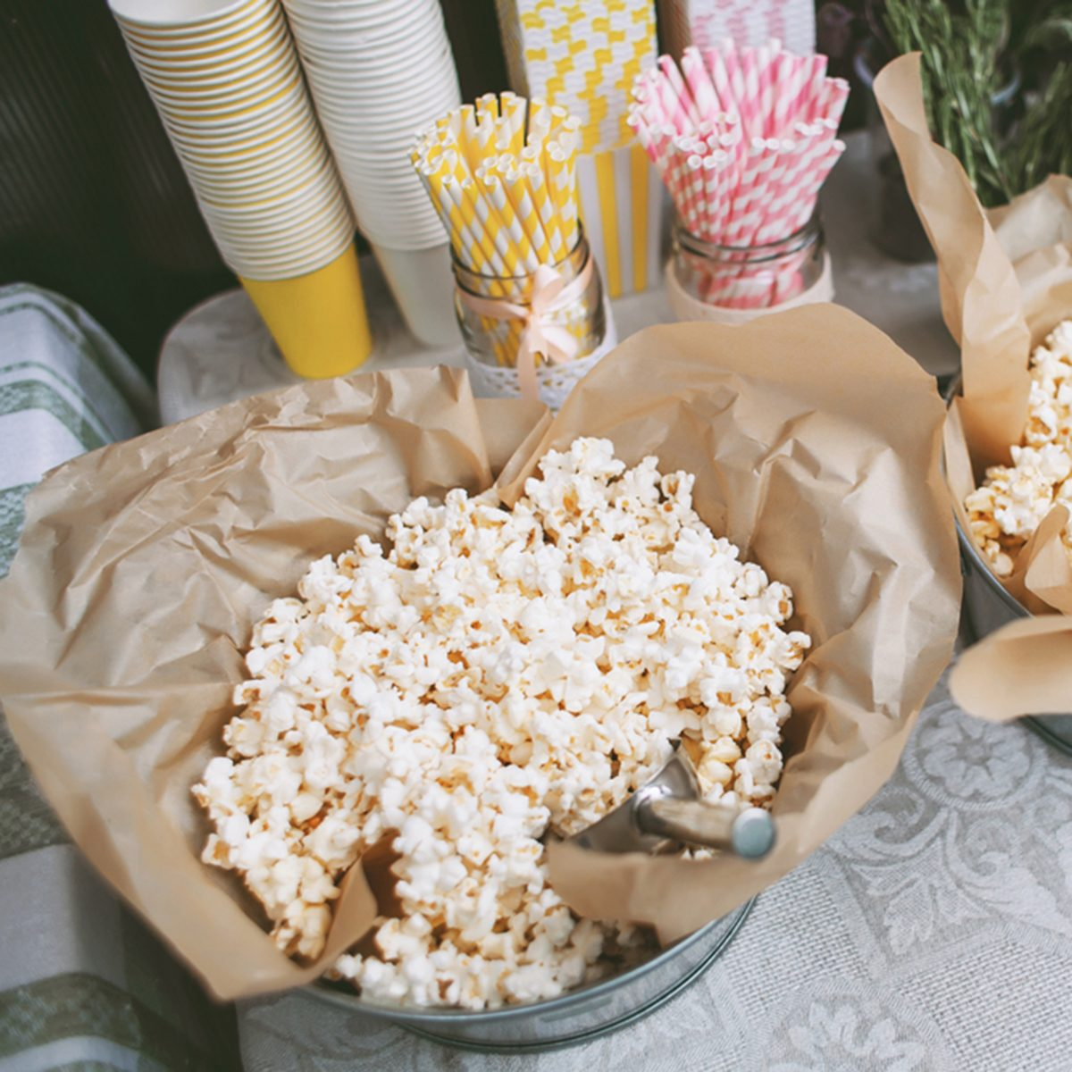 Details of a tasty candy bar with buckets of popcorn and pasteboard pink and yellow glasses